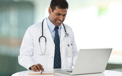 Indian doctor working on his laptop.